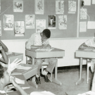 Archival photo of deaf students and teacher in a classroom
