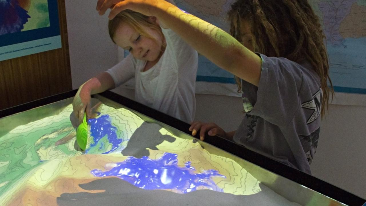 Children play with the AR sandbox