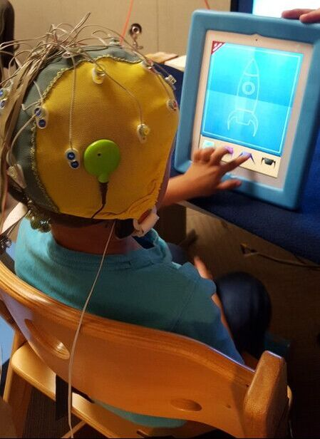 Photo of a child wearing a cap with electrodes and responding to images on a computer screen