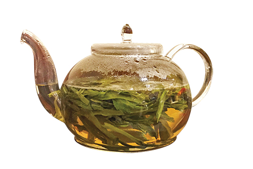 Photo of glass tea pot with tea leaves steeping in water