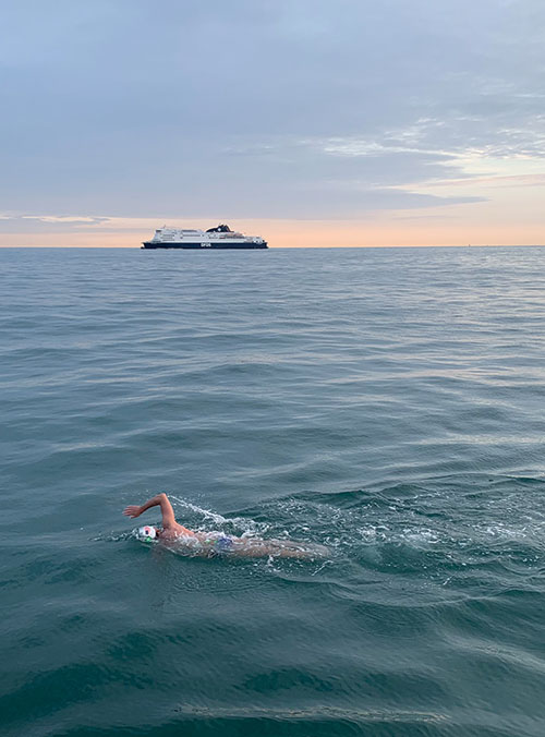 Photo of swimmer in the English channel, ship in the background going opposite direction.