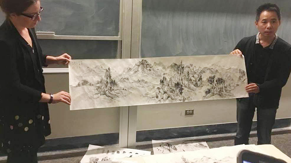 Visiting scholar Zhao Panchao, right, an art historian and artist from Minzu University in Beijing, holds his landscape hand scroll with the help of Anna Glaze, a visiting instructor. (UC Davis)