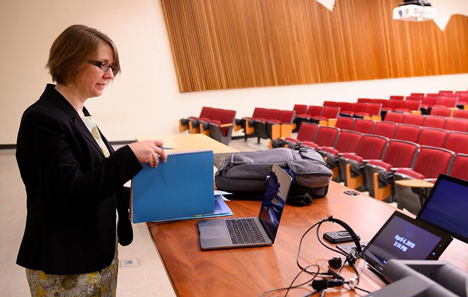 Photo of UC Davis professor Emily Merchant looking at her papers in a lecture hall.