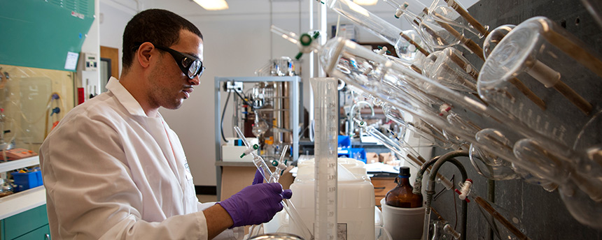 Pharmaceutical chemistry major Manuel Munoz '13 prepares a liquid solution for his intern project on cancer research, getting research experience that graduate programs are seeking. (Gregory Urquiaga/UC Davis)