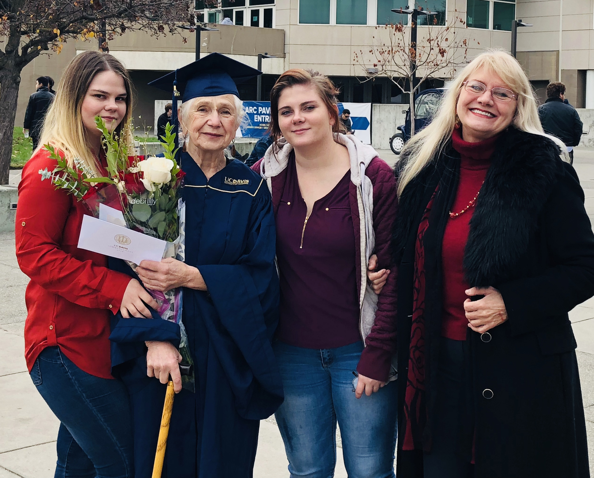 Photo of Marianna Daniel in cap and gown with her family in front of the UC Davis ARC Pavilion