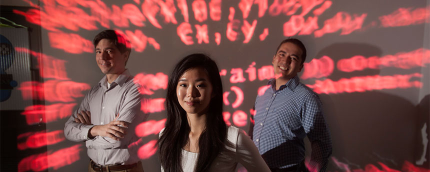 Colin Milburn, left, professor and incoming chair of the Science and Technology Studies Program, stands amid red computer code in the ModLab with student Ashley Han, center, and Gerardo Con Diaz, an assistant professor in the program. (Gregory Urquiaga/UC Davis)