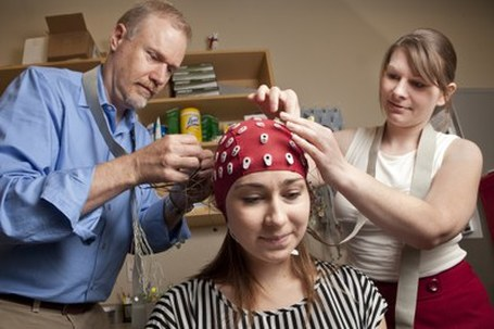 Photo of researchers attaching electrodes to a cap on someone's head.