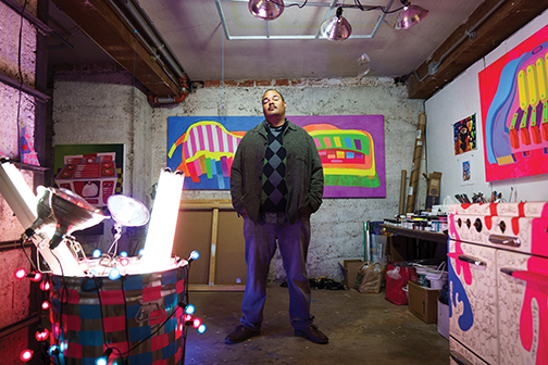 Photo of artist surrounded by his artworks in his studio