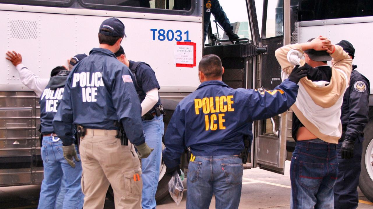 Photo of immigration officials making arrests by a bus