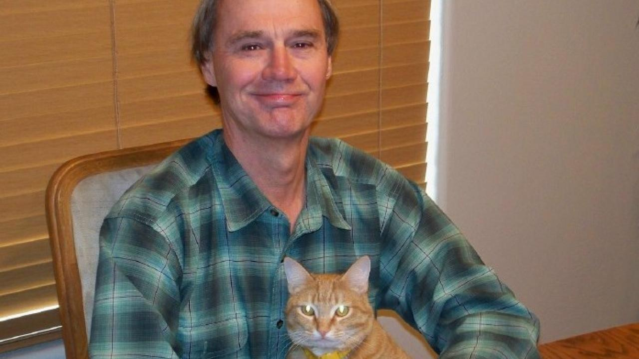 Portrait photo of UC Davis political science alum and author Tom Garrison with cat