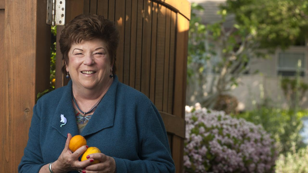Photo: Eastin, with oranges in hands, standing in front of her garden gate