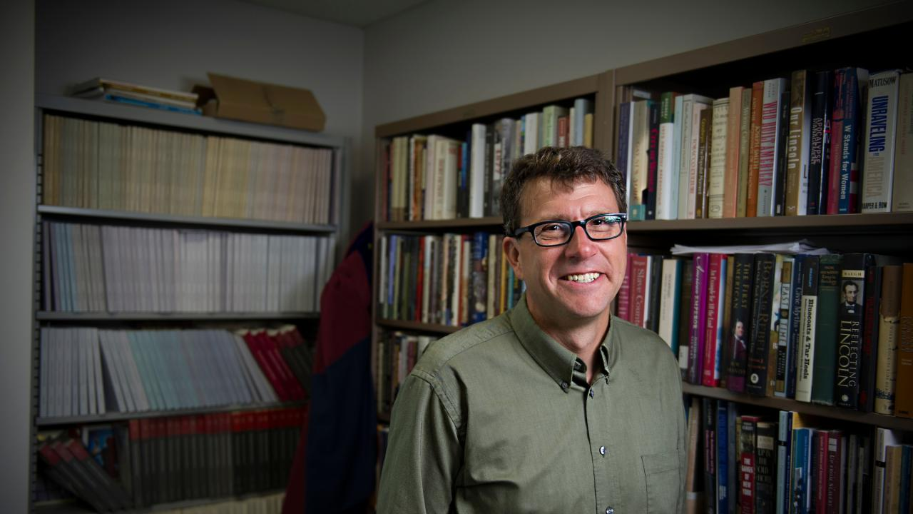 Photo of historian Gregory Downs standing in front of bookshelves