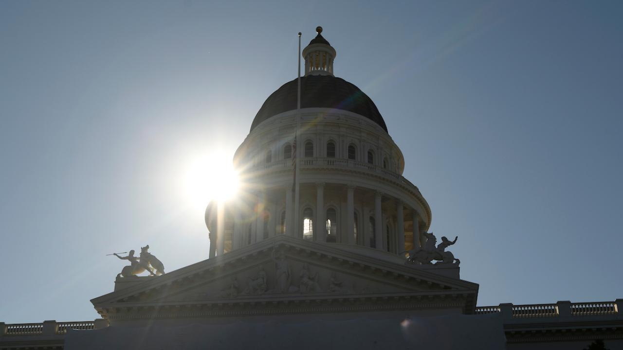 State capitol dome in Sacramento, with sun behind.