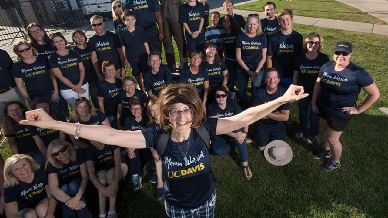 Photo of Janice Corbett, smiling and arms stretched wide, with crowd of friends behind her.