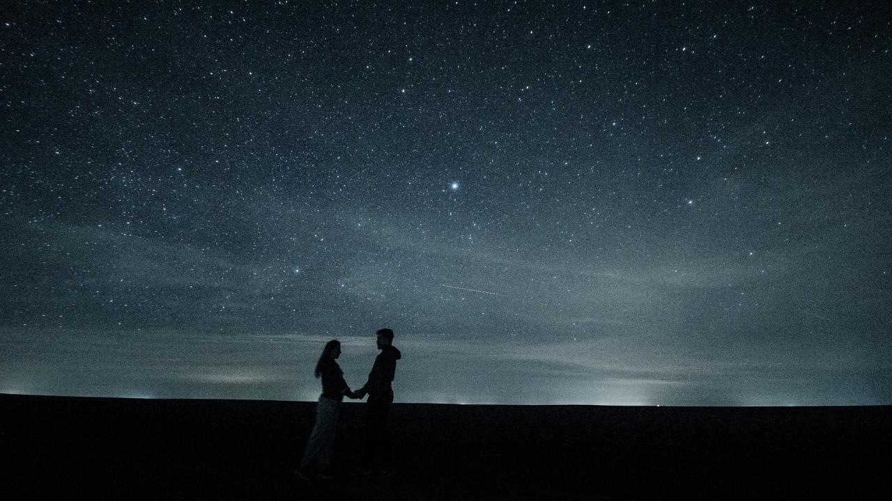 Photo: Couple facing each other, holding hands, with starry night sky in background.