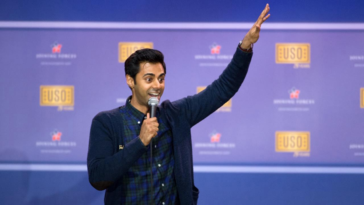 Photo: Hasan Minhaj gesturing with a raised hand during a show.