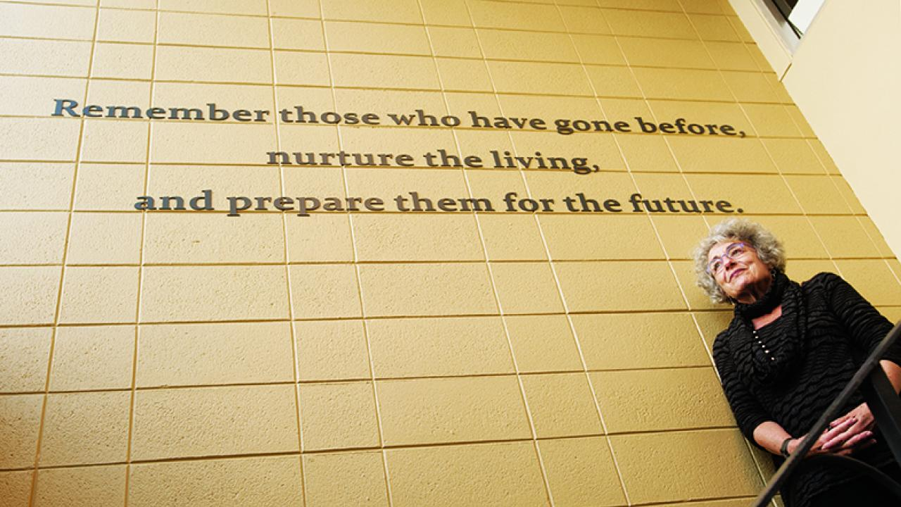 "Photo: historian under sign, ""Remember those who have gone before, nurture the living and prepare them for the future."""