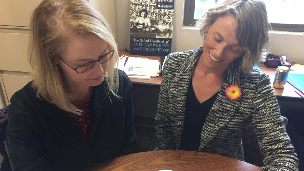 Photo of two UC Davis faculty looking at book on table