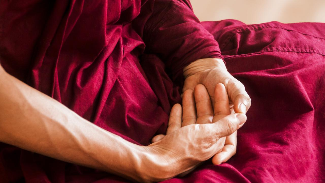Photo of folded hands of meditating monk