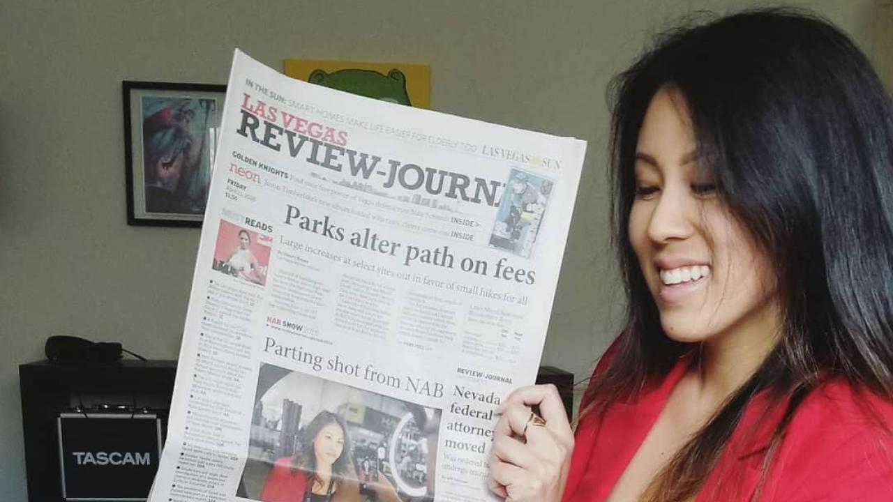 Photo: Nicki Sun looking at Las Vegas newspaper with photo of her on the front page.