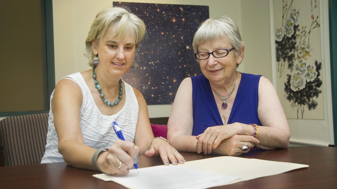 Interim Dean Alex Navrotsky and Department Chair Susan Kauzlarich sign the Green Chemistry Commitment.