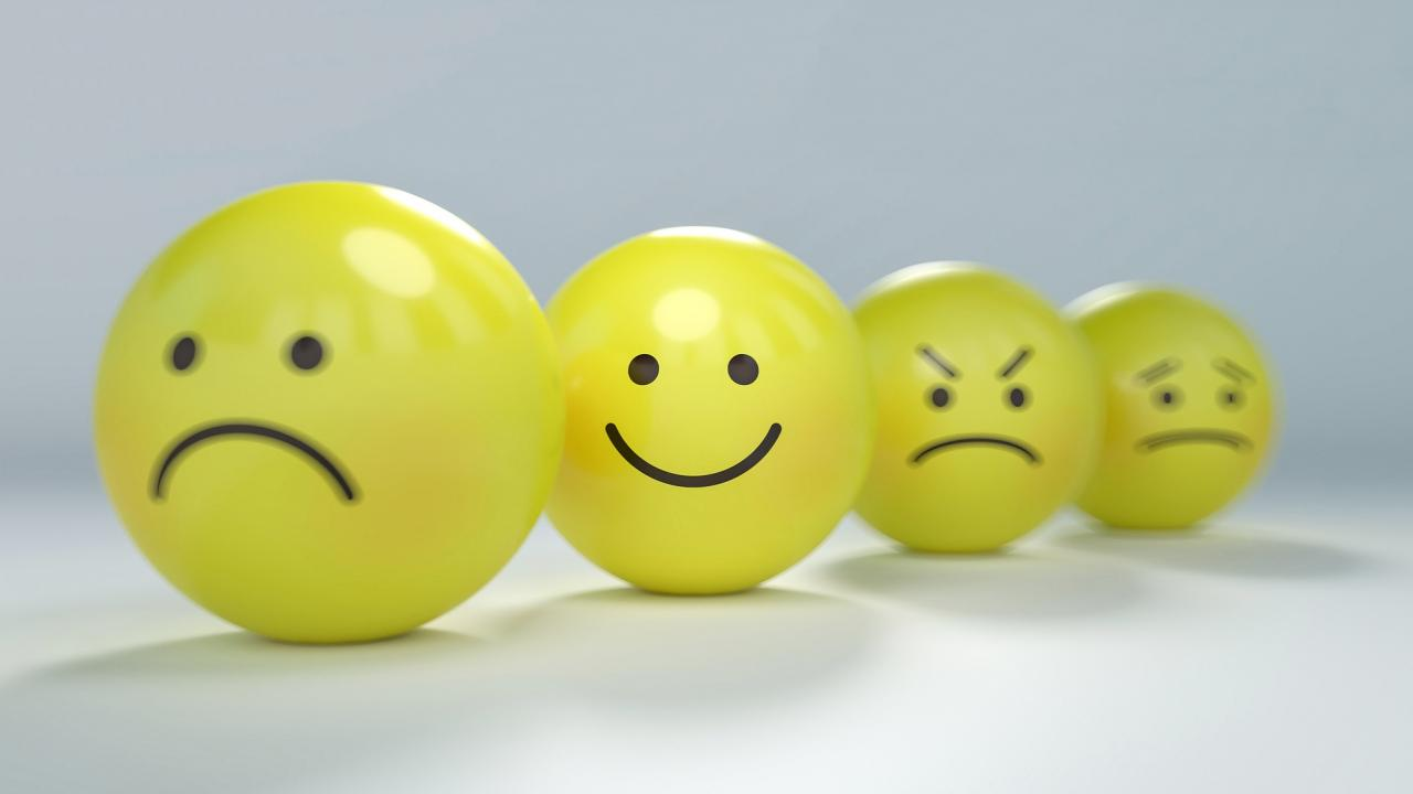 Four emoji-style balls, with one smiling and the others frowning