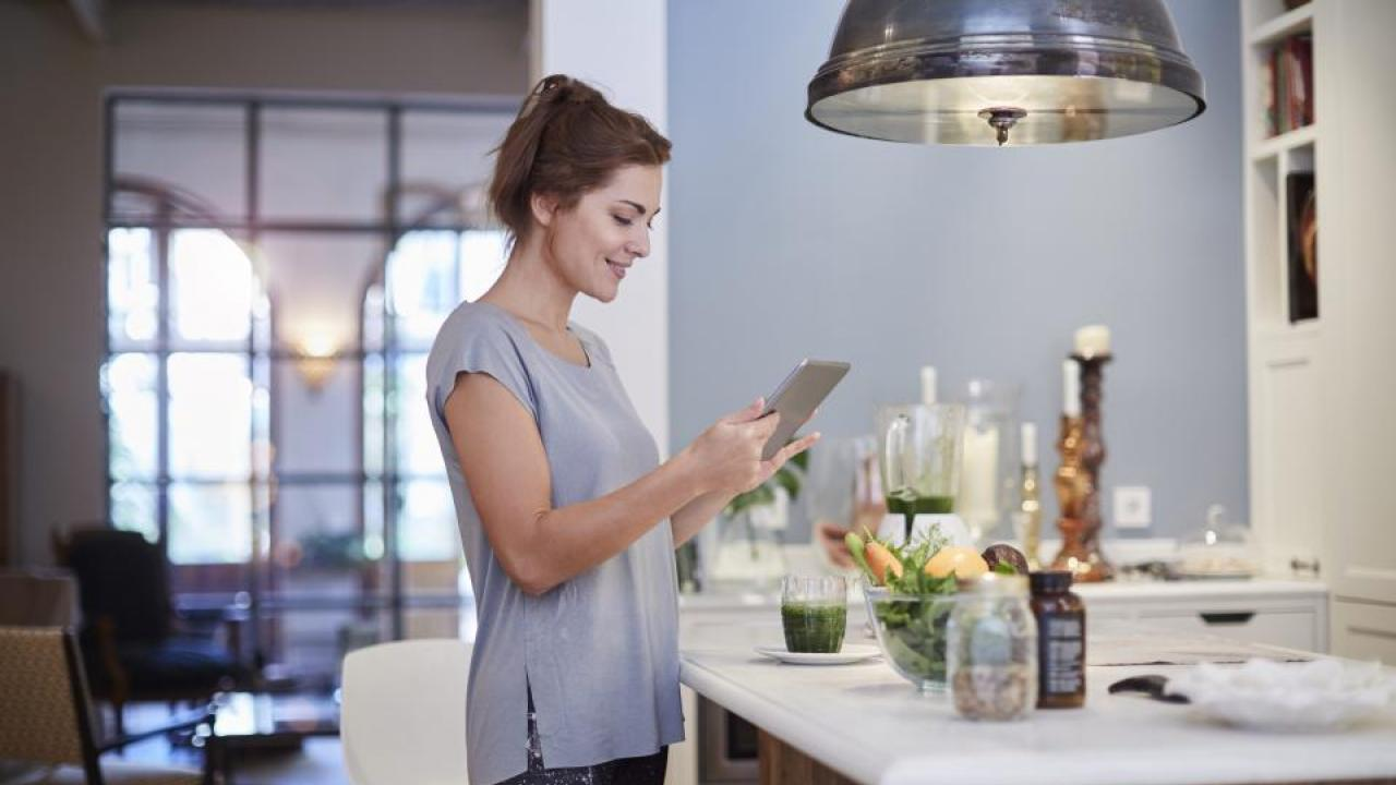 Woman standing in kitchen and looking at a tablet.