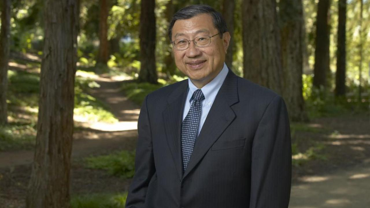 Photo of UC Davis physicist and former dean Winston Ko, wearing a suit, standing in a UC Davis redwood grove.