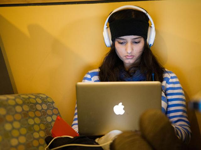 A UC Davis student studies on her laptop.