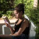 Photo: young woman sitting on a bench reading a book