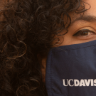 Photo of young woman wearing a face mask with UC Davis printed on it.