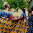 Women, one holding a colorful wrap, and another carrying a baby on her back, line up at a health clinic in Tanzania.