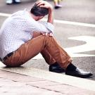 Photo of dejected man sitting on curb, head in hand