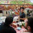 Photo of UC Davis muralist and two students, with mural in background and paints on table in foreground.
