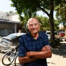 Photo of Bob Dunning with arms folded, standing on downtown Davis sidewalk, Varsity Theater, bikes and parked cars in background.