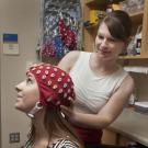Photo of researcher adjusting an EEG cap on a young woman.