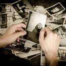 Photo: adult looking at old photo of child