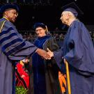 Photo of elderly woman in UC Davis graduation robes shaking hands with chancellor on commencement stage
