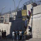 People climbing over barrier in Palestine
