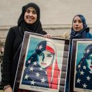 Two Muslim women holding posters of woman wearing stars and stripes hijab