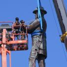 workers in a cherry picker next to statue