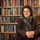 Portrait photo of UC Davis professor sitting in front of a wall of books.